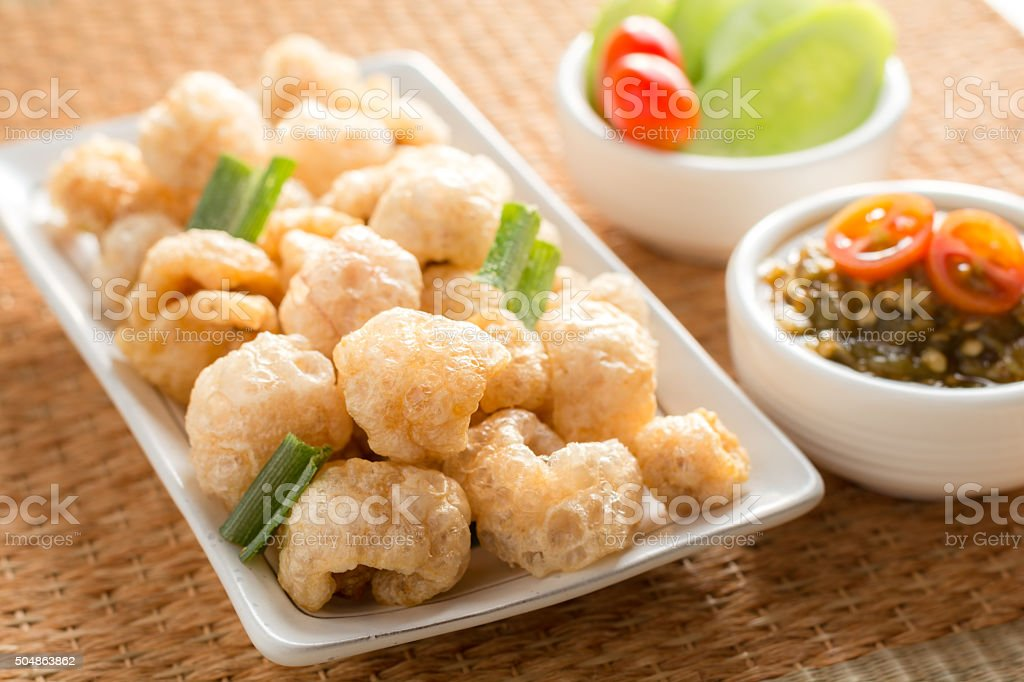 Cracklings fried appetizers served with sauce and vegetable. stock photo
