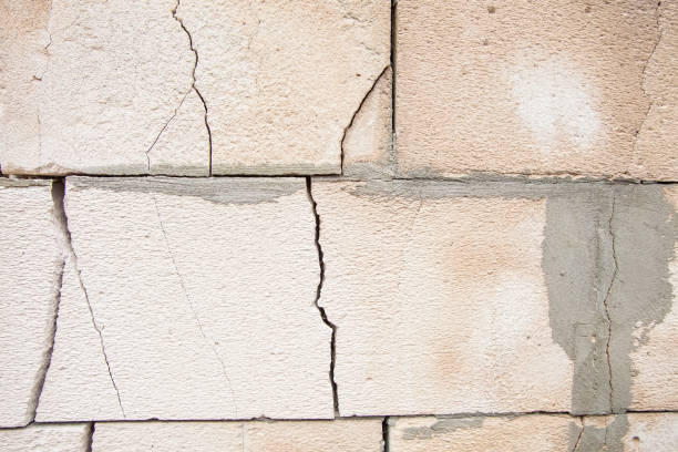 Cracks on the white wall blocks. The destruction of the wall. Background texture stock photo