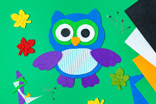 Craft, applique of an owl from multi-colored felt on a green background. Creative activities at home with children. Sewing soft toys, hobby. Workplace. Felt bird, owl, big eyes. Flat lay, top view.