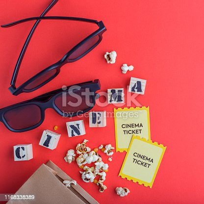 956942702 istock photo craft bag with popcorn 3d cinema glasses tickets wooden cubes with text on red background creative flatlay 1168338389