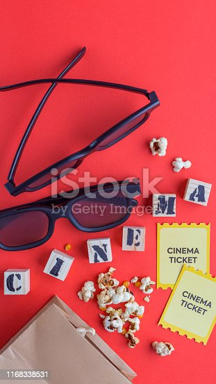 956942702 istock photo craft bag with popcorn 3d cinema glasses tickets wooden cubes with text on red background creative flatlay 1168338531