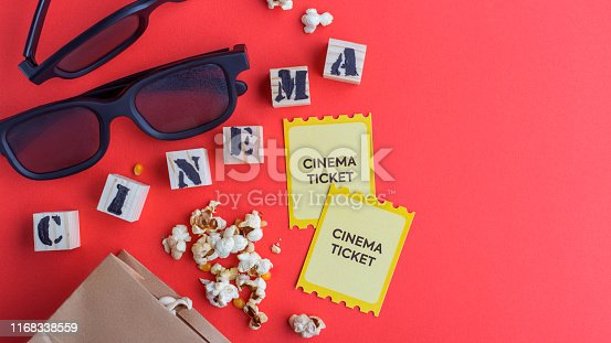 956942702 istock photo craft bag with popcorn 3d cinema glasses tickets wooden cubes with text on red background creative flatlay 1168338559