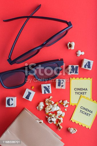 956942702 istock photo craft bag with popcorn 3d cinema glasses tickets wooden cubes with text on red background creative flatlay 1168338701