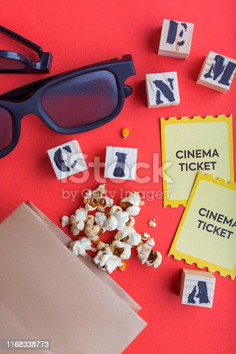 956942702 istock photo craft bag with popcorn 3d cinema glasses tickets wooden cubes with text on red background creative flatlay 1168338773