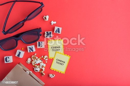 956942702 istock photo craft bag with popcorn 3d cinema glasses tickets wooden cubes with text on red background creative flatlay 1168338807