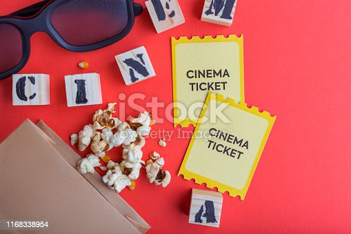 956942702 istock photo craft bag with popcorn 3d cinema glasses tickets wooden cubes with text on red background creative flatlay 1168338954
