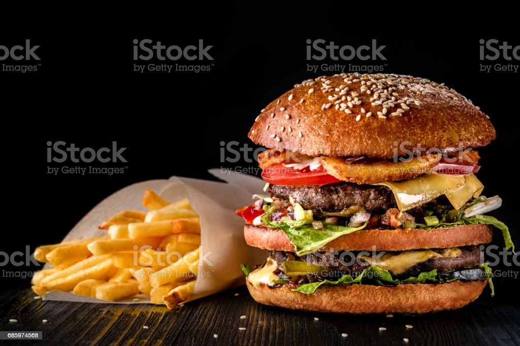 Craft beef burger and french fries on wooden table isolated on black background stock photo