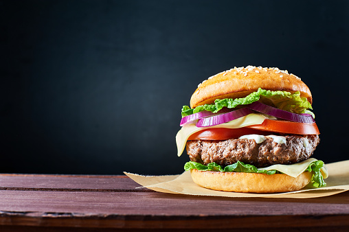Craft beef burger on wooden table isolated on dark blue background.