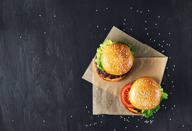 Craft beef burgers with vegetables. Craft beef burgers with vegetables. Flat lay on black textured background with sesame seeds. overhead stock pictures, royalty-free photos & images