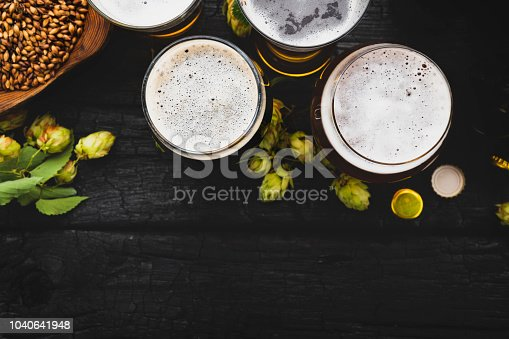Beer with ingredients on black wooden table. Top view