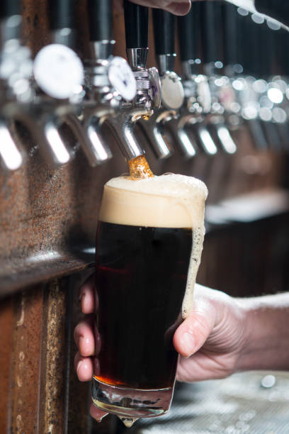 craft beer pint pour - dark beer stock photos and pictures