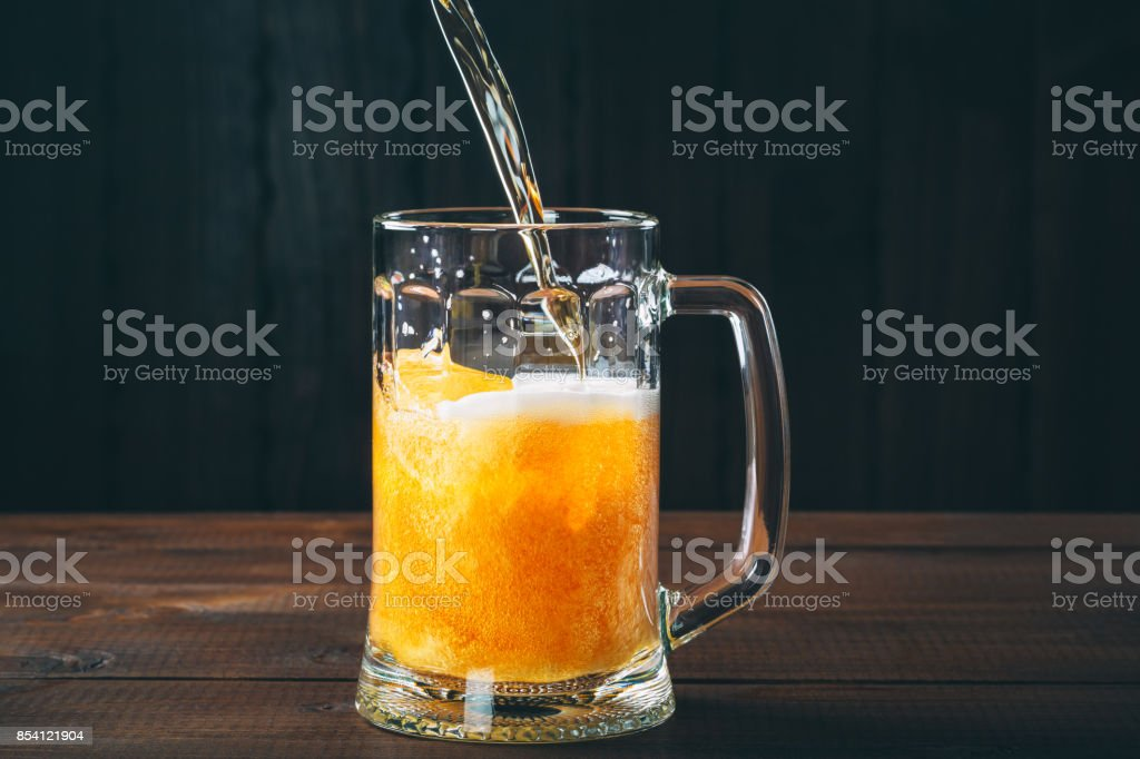 Craft beer poured into a pint glass on the wooden background stock photo