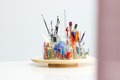 Verschiedene Bastelmaterialien sind bereit benutzt zu werden. Sie stehen auf einem weißen Tisch. Bunde stifte und viele Farben sind vorhanden.