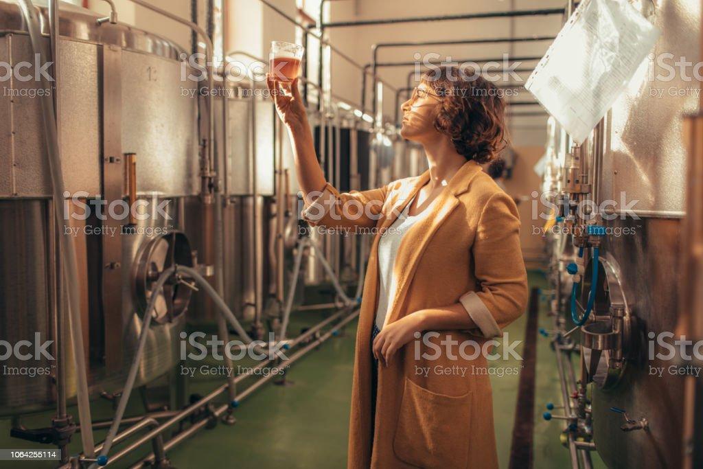 Brew master testing beer in brewery.