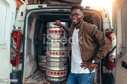 Young businessman standing by the kegs.
