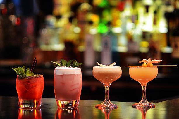oficio variedad de cócteles en el bar bien iluminada - cóctel fotografías e imágenes de stock