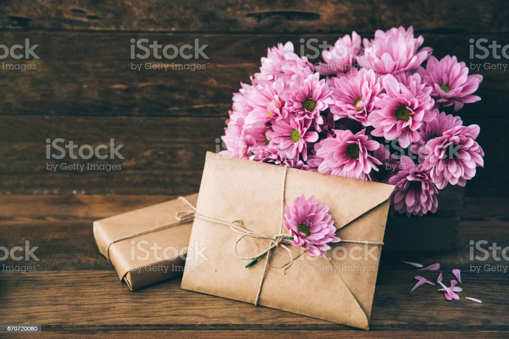 Craft envelope and flowers over wooden background. Space for text - foto de stock