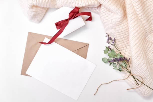 handwerk-umschlag, papier leer, geschenkbox mit bogen, schal, getrocknete blumen und blätter auf weißem hintergrund. winter urlaub konzept. flach legen, top aussicht, textfreiraum - winterdeko basteln stock-fotos und bilder