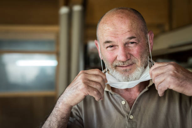 Craft men 60-65 years in his workshop smiling after isolation, head shot - stock photo