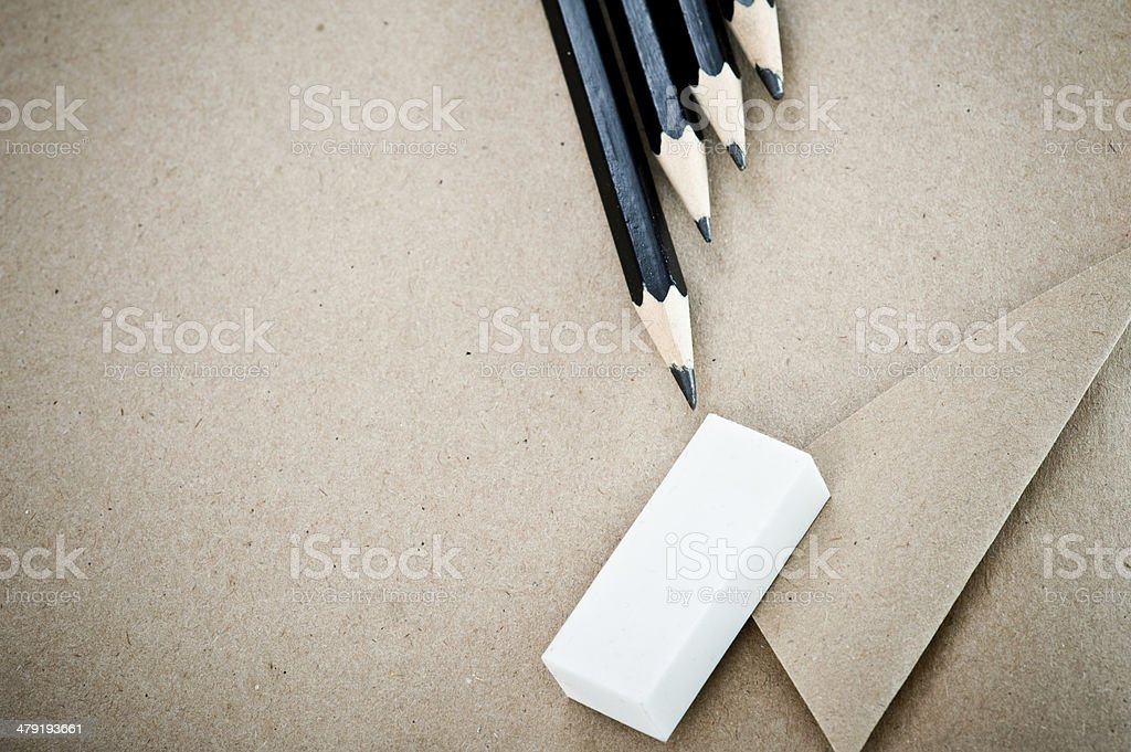 Shabby craft paper background with pencils and eraser