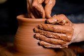 Hands of potter making clay pot, closeup photo