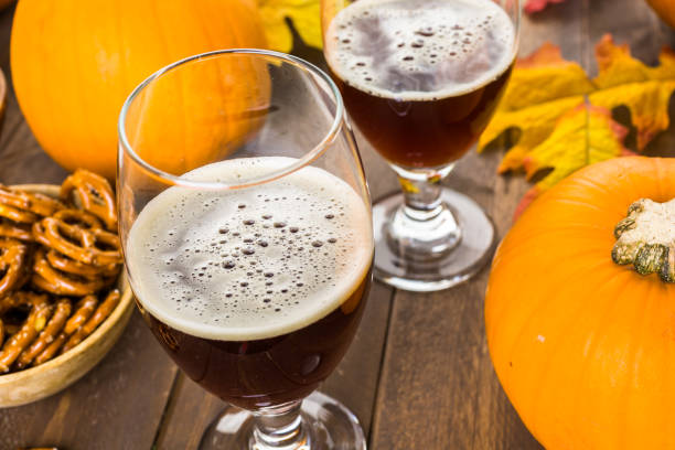 Craft pumpkin beer Craft pumpkin beer in beer glasses with salty pretzels and popcorn. ale stock pictures, royalty-free photos & images