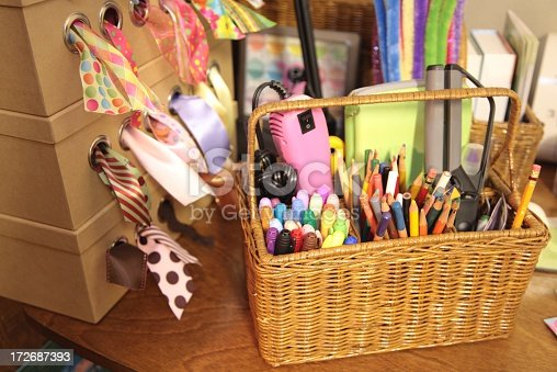 Basket with colorful pencils, markers, and other craft supplies. There is a dispenser with colorful ribbon next to basket. Horizontal image. Check my portfolio for more images of this well organized craft area.