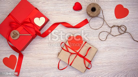 1125461272 istock photo Craft Valentines gift box with red paper hearts on wooden background, holiday 1125461288