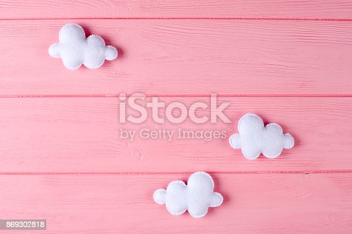 istock Craft white clouds with frame, copyspace on pink wooden background. Hand made felt toys. Abstract sky. 869302818