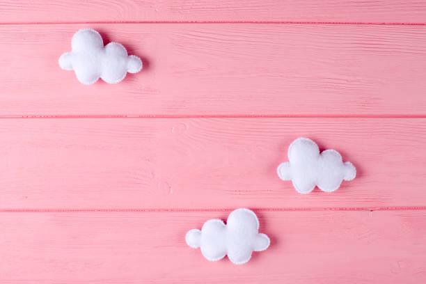 fertige weiße wolken mit rahmen, exemplar auf rosa hintergrund aus holz. handgemachte filz spielzeug. abstrakte himmel. - filzunterlage stock-fotos und bilder