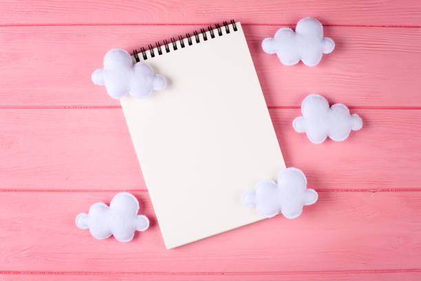 Craft white clouds with notebook copyspace on pink wooden background picture id869302830?b=1&k=6&m=869302830&s=612x612&w=0&h= sq7vld3 3pq85mkerjujob3782g7msgvte1 qajliu=