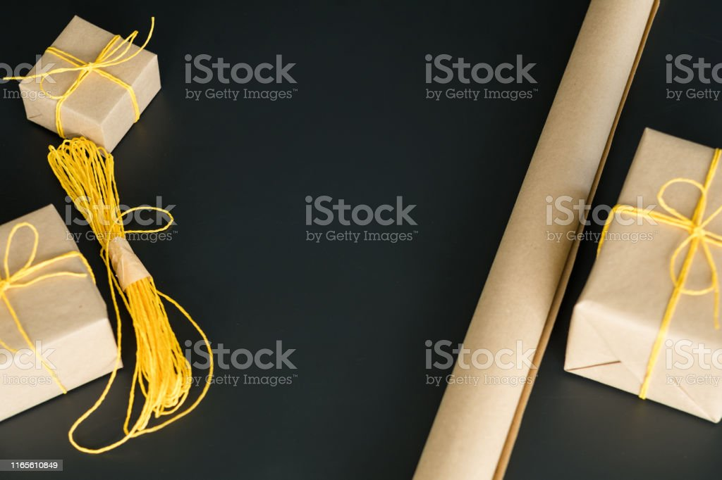 Craft workshop. Flat lay of beige wrapping paper, yellow cord,...