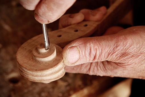 Violin maker working on a scroll.