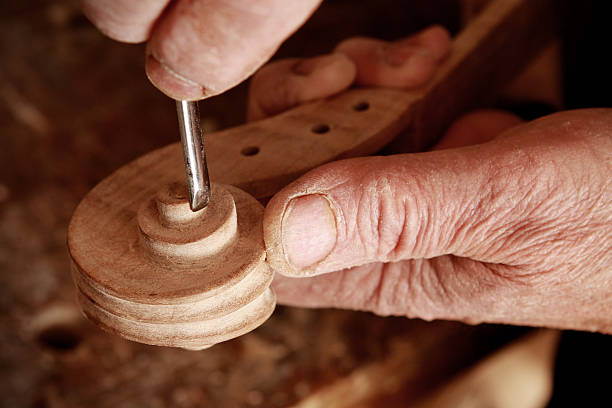 A crafted skilled violin creator Violin maker working on a scroll. carving craft product stock pictures, royalty-free photos & images