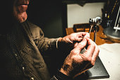 A fly fisherman ties a fly for fly fishing in his workshop. Horizontal image, with focus on the detail of his hands and gear.