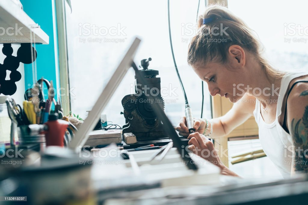 Female Jeweler crafting silver jewelry in workshop