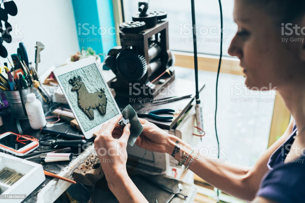 Female Jeweler using digital tablet while crafting silver jewelry in...