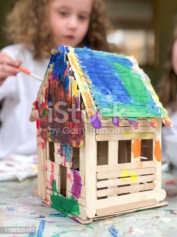 A happy little girl is painting a house built from popsicle sticks.