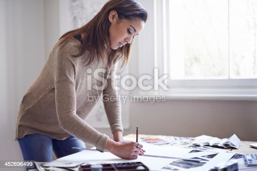 A young woman working on her portfolio at home