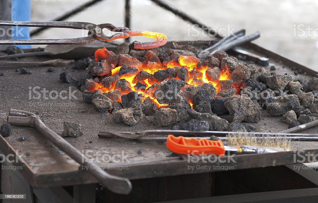 Craftsman blacksmith warming a horseshoe of iron in the fire royalty-free stock photo