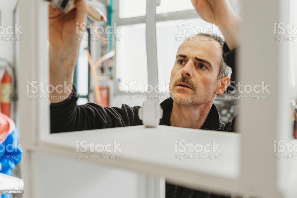 Handwerker-Schreiner einen Rahmen mit Pinsel malen Lizenzfreies stock-foto
