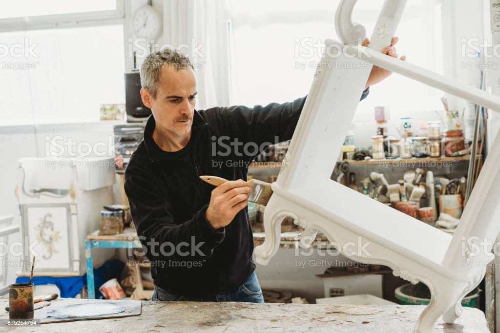 Craftsman carpenter painting a frame with brush stock photo