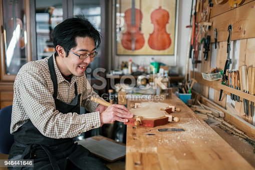 Craftsman carving a violin. Tokyo, Japan. January 2018