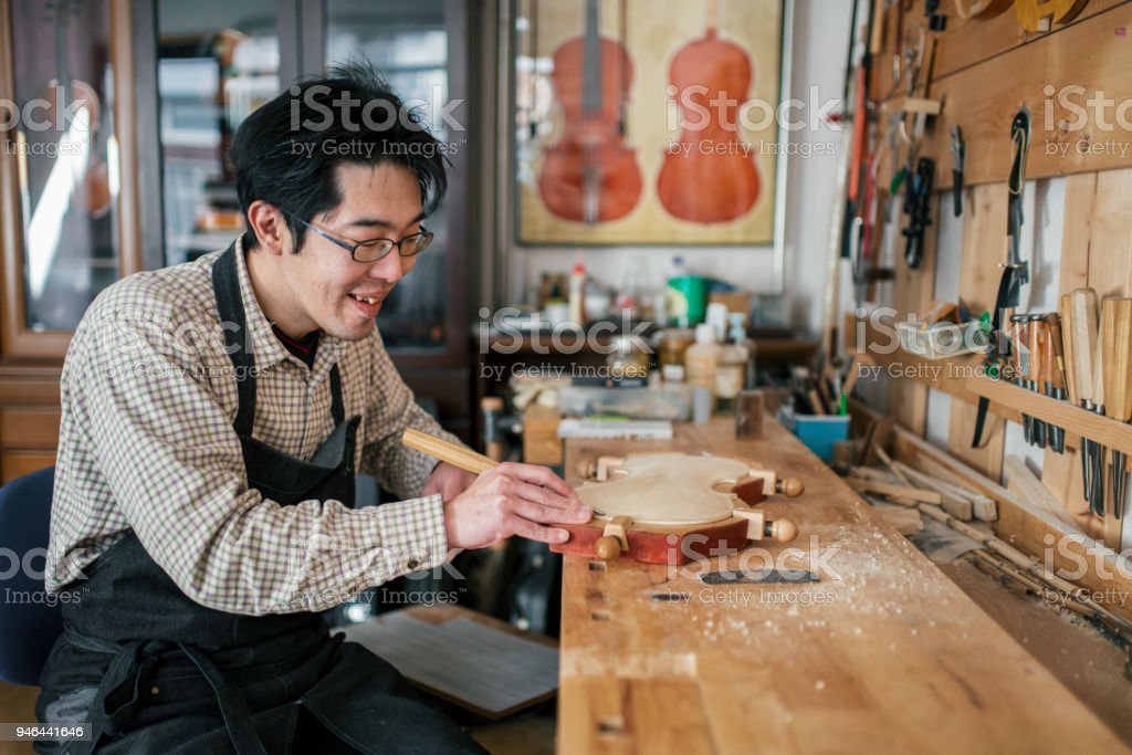 Craftsman carving a violin stock photo