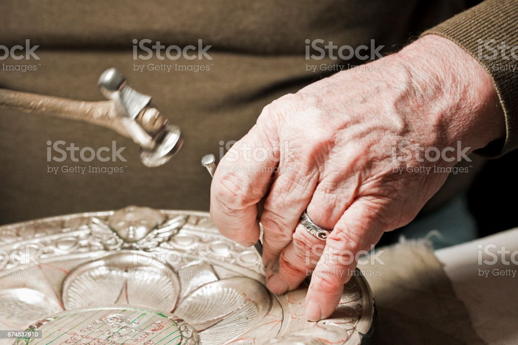 Craftsman carving patterns on the metal plate (Florence, Italy, Europe) stock photo