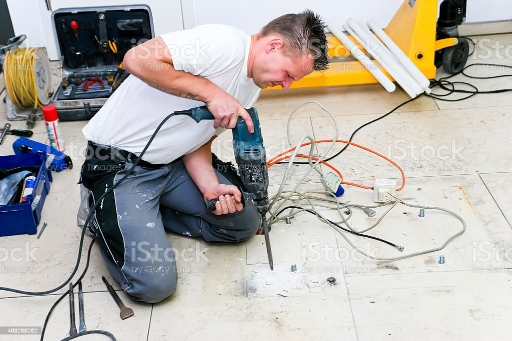 Craftsman chiseling holes in marble floor stock photo