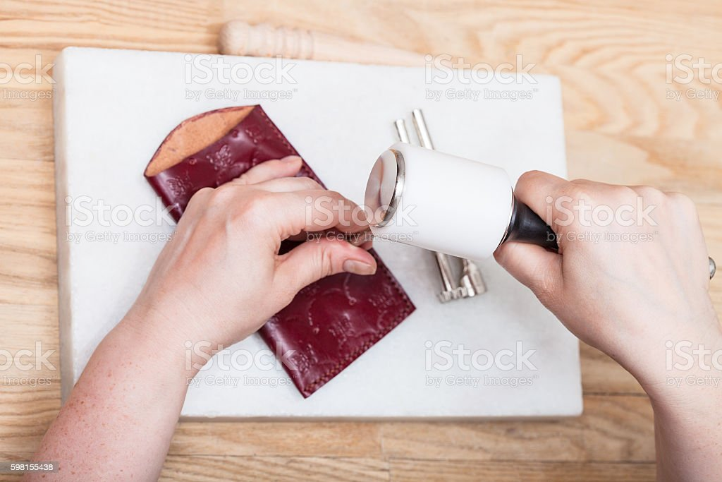 craftsman corrects embossing of leather pouch stock photo