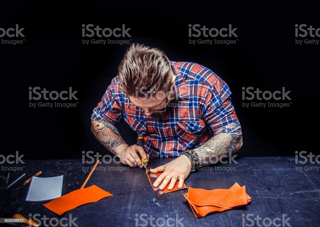 Craftsman creating a new leather product at the tanner shop stock photo