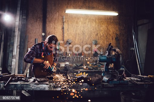 Blacksmith working with power tools and cutting metal with angle ginder in workshop