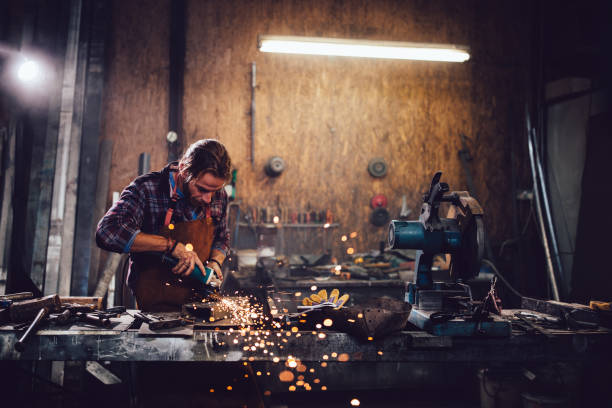 Craftsman cutting metal and using angle grinder in workshop Blacksmith working with power tools and cutting metal with angle ginder in workshop workbench stock pictures, royalty-free photos & images